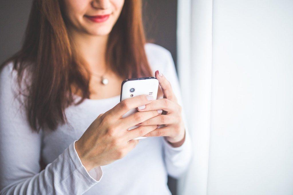 donna con cellulare in mano gruppi whatsapp di classe